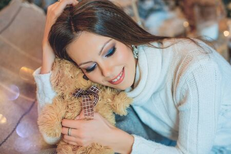 Beautiful young girl in a white sweater hugging a teddy bear