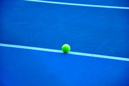 individual sport: Tennis Ball on the blue tennis Court Stock Photo