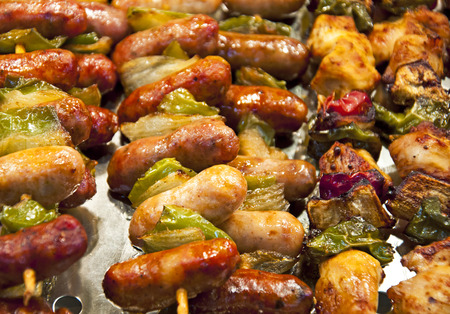 Mini sausage with toppings of meats and veggies - traditional street food at local markets in Spain. Shallow depth of field Stock Photo