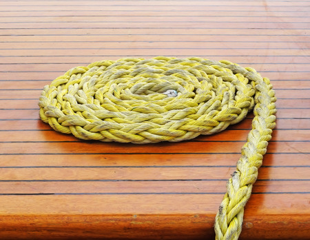 Close-up of a  rope with a knotted end tied around a cleat on a wooden pier Nautical rope