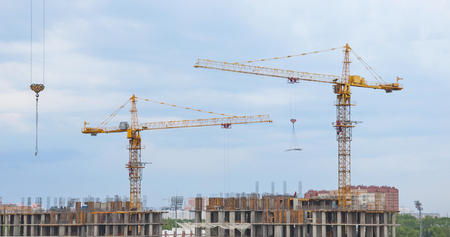 Tower cranes on a background of sky and clouds Stock Photo