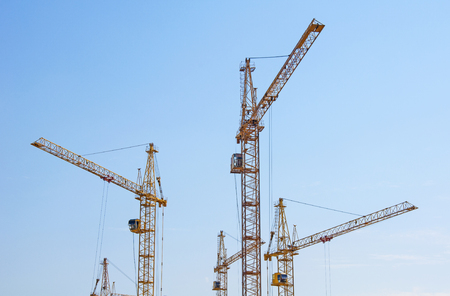 dwelling: Tower cranes on a background of blue sky