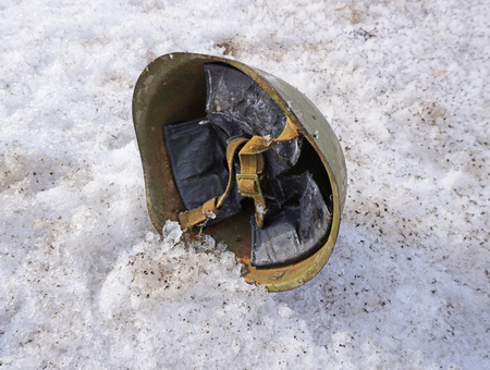soldiers helmet lying on the snow in the afternoon