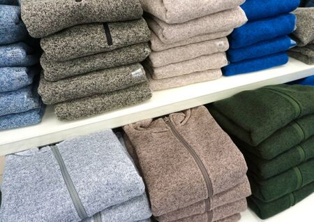 different color sweaters are on the shelf in the store