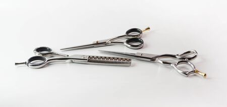 Hairdressing different scissors isolated on white background. Hairdressing  scissors equipment on table in professional hairdressing salo.                                                                                              Imagens