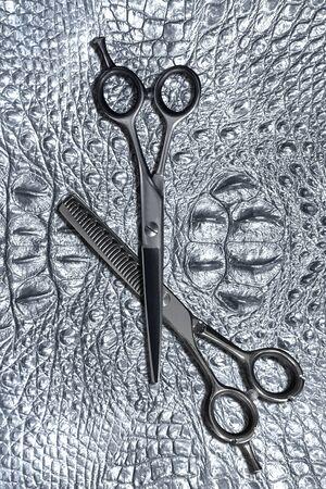 hairdressing different scissors isolated on silver crocodile skin background.  Standard-Bild