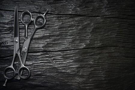 hairdressing different scissors isolated on dark wood background.  Standard-Bild