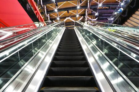 The interior of the airport. Escalator going up and down.