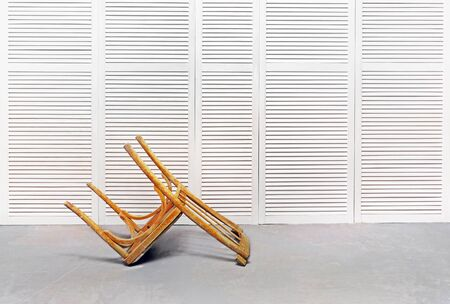 An old wooden chair in an empty room against a white wall