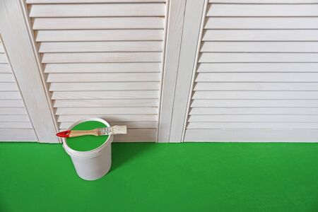 a can of paint and a brush stand against a white wall on the green floor