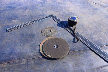 Construction site with measuring tool, square and discs for power tools