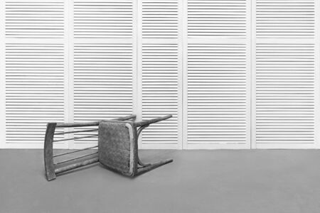 An old wooden chair lies in an empty room against a white wall Stock Photo