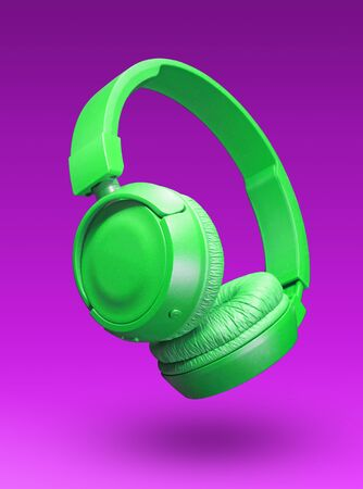 Green headphones isolated on a violet