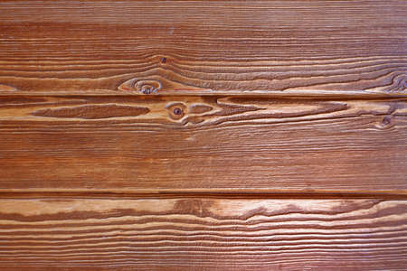A fragment of a old wooden plank Horizontal boards are tightly nailed to each other and provide reliable