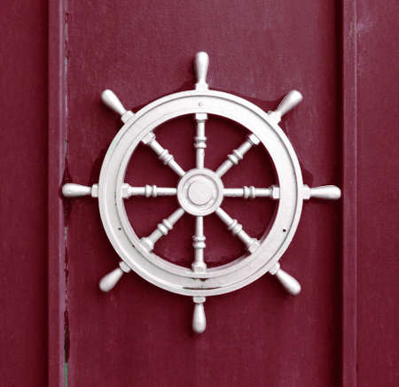 A steel ship wheel on a red background. Marine decorations on the wall