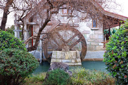 Water mill wheel on river on rainy day. Sustainable energy and water power traditional machinery Stock fotó