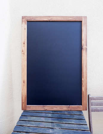 an empty writing board sits on a wooden table against the wall Stock fotó