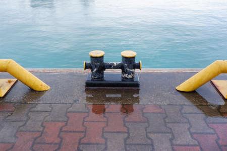 Marine black mooring bollard on a dock by the waters edge