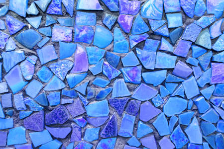 Blue mosaic tiles of irregular sizes arranged in a background motif. Space for text.