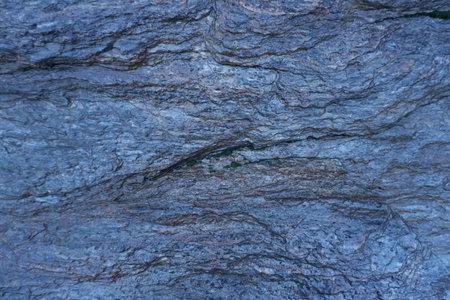 Dark blue wet slate background or texture.