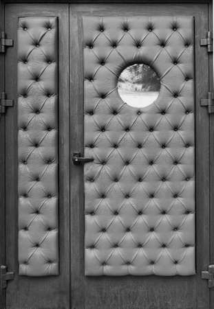 metal door with round window with old dark-colored upholstery