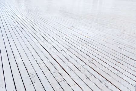 Wet wooden floor is made of white planks extending into the distance