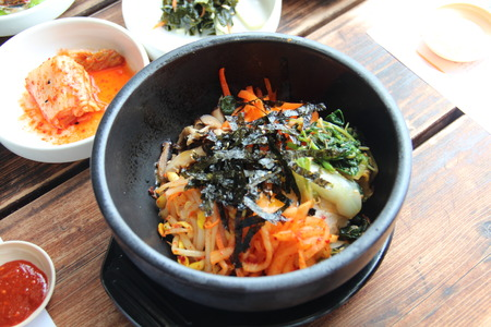 Korean bibimbap served on a wooden table with Korean side dishes photo