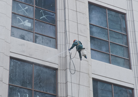 colum: A worker is washing the building located in shanghai Editorial