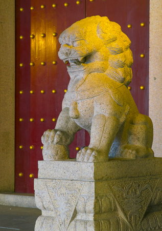 Chinese stone lion infront door at night