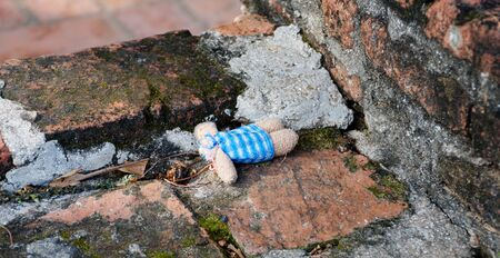 An abandoned headless doll laying on the bricked floor. Stock Photo