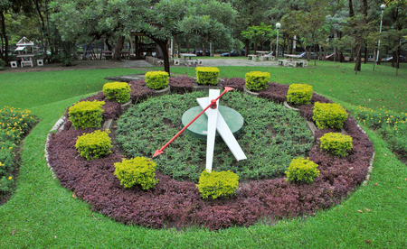 The garden decorated with a big clock on a small hill. Time running acurate to the time zone standard, not just an disguised clock.