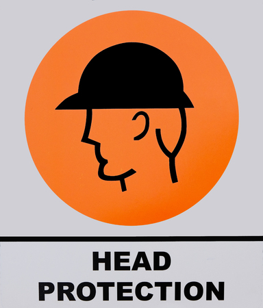 building regulations: Head protection sign on white and orange background. This photo was taken from the sign board, it is not an illustration work.