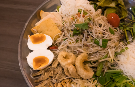 Delicious Thai papaya salad with various Thai side dishes, placed on stainless steel tray, called Somtum Tard in Thai language.