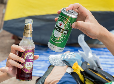 BANGKOK, THAILAND - May 27, 2017: Photo of tourist hands holding a bottle of Full Moon wine and a Heineken beer can in the party celebration in Bangkok, Thailand on May 27, 2017.
