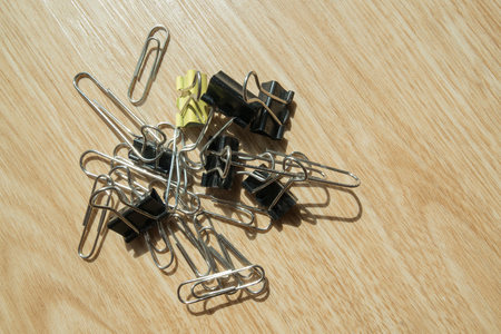 fasten: Several paper clips on wooden background.