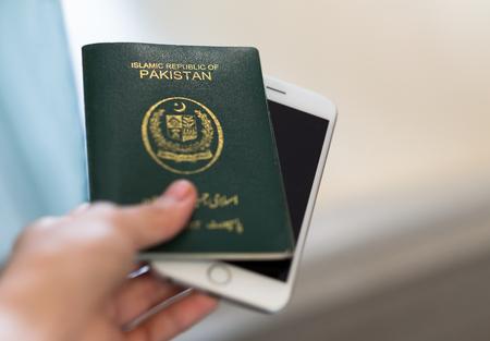 A hand holds Pakistan passport. Focus on the font on passport.
