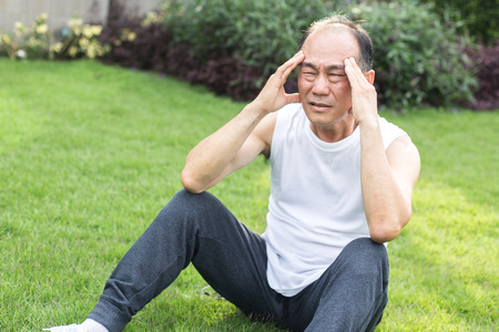 Asian old man headache and sitting in the grass , man stress and headache  concept.
