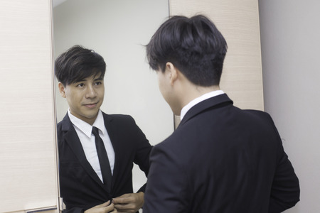 miror: Young asian businessman doing up his tie knot in a mirror.