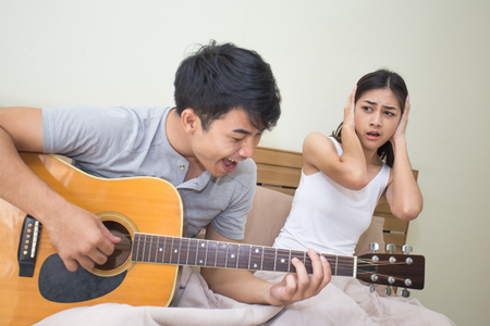 Asian woman annoyed at a man who is singing and playing a guitar. 스톡 콘텐츠