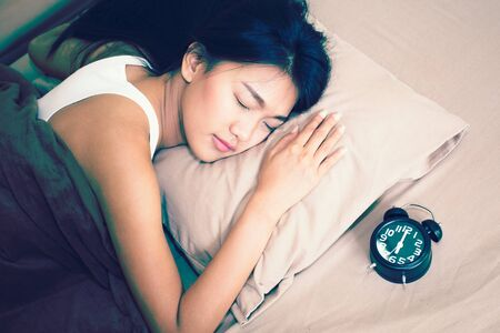 Beautiful asian woman sleep with vintage clock, Young woman Portrait in bedroom, vintage color tone.