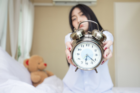 Hand woman holding alarm clock on morning.