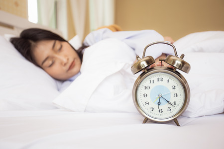 アジア系の若い女性と自宅で寝ているコンセプトは、20 代女性の寝室の目覚まし時計を眠っている歳。