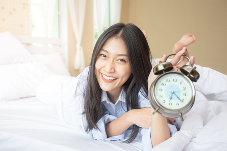 Happy young asian woman hold clock with attractive smiling, 20s year old. Banque d'images