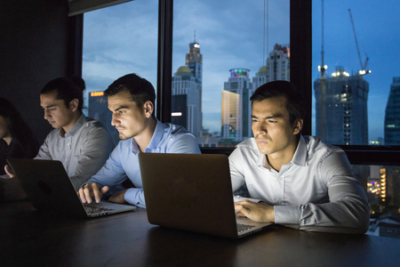 business team working late at night with lights off and computers laptop screen light on. Business people working hard concept. 20-30 year old. Stock Photo - 79412211