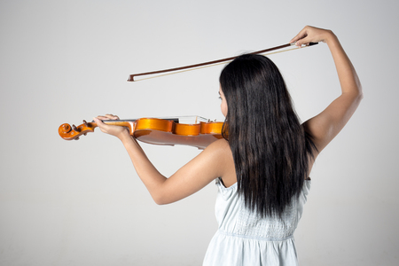 Asian woman playing the violin. 20-25 year old.