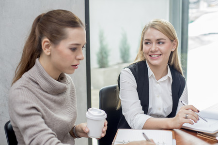conection: Young woman working together in modern place. Business people takling in modern office. Greeting deal concept