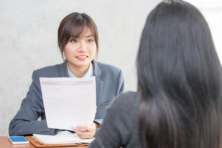 Young Asian woman arriving for a job interview. Business people takling in modern office. Greeting deal concept 스톡 콘텐츠
