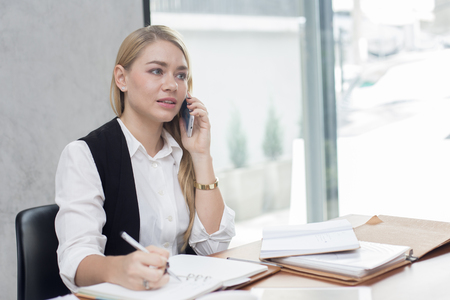Young woman using smartphone for work at modern place, Business people takling in modern office. Greeting deal concept Banque d'images