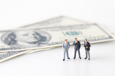 Miniature model group of businessman thinking with project for investment standing together on money.