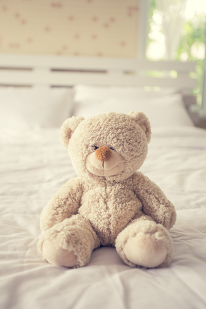 Teddy bear with depression sitting on the bed, vintage color tone.